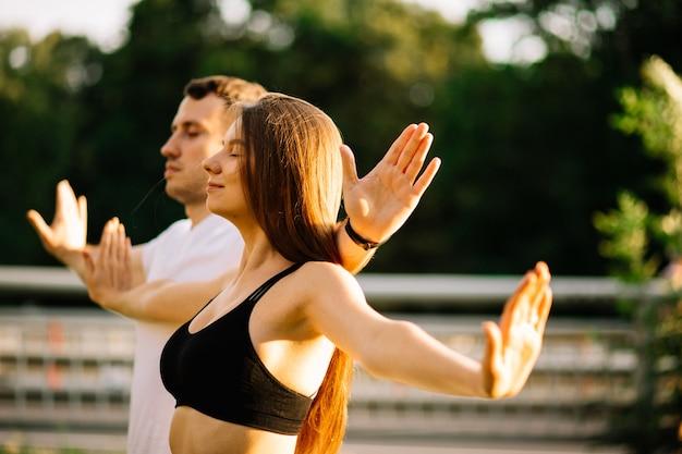 젊은 부부 남녀는 서서 일몰에 함께 명상하고, 잔디밭에서 요가, 여름 저녁, 도시 생활 방식, 호흡 운동