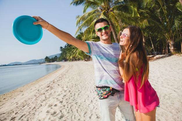 熱帯のビーチ、夏休み、愛、ロマンス、幸せな気分、笑顔、楽しんで、流行に敏感な服、サングラス、デニムのショートパンツ、日当たりの良い、ポジティブな気分でフライングディスクを再生する若いカップルの男性と女性