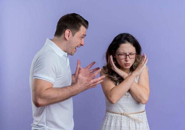 彼女が青い壁の上に立っている手を交差させる一時停止の標識を作っている間、彼のガールフレンドに叫んでいる男と喧嘩している若いカップルの男性と女性