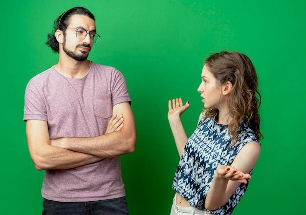 Молодая пара мужчина и женщина ссорятся, женщина расстроена, разговаривает со своим парнем, стоя со скрещенными руками, хмурясь над зеленой стеной