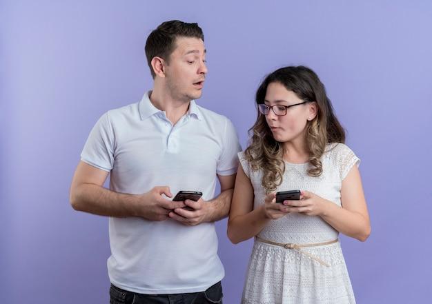 젊은 부부 남자와 여자는 파란색 벽에 함께 서 스마트 폰을 들고 서로 감시