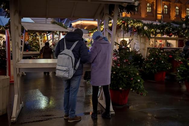 Молодая пара мужчина и женщина стоят за столом в фудкорте на новогодней ярмарке на рыночной площади