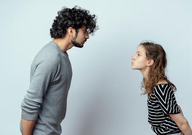 向かい合って立っている若いカップルの男性と女性が白い壁の上でお互いにキスしようとしています