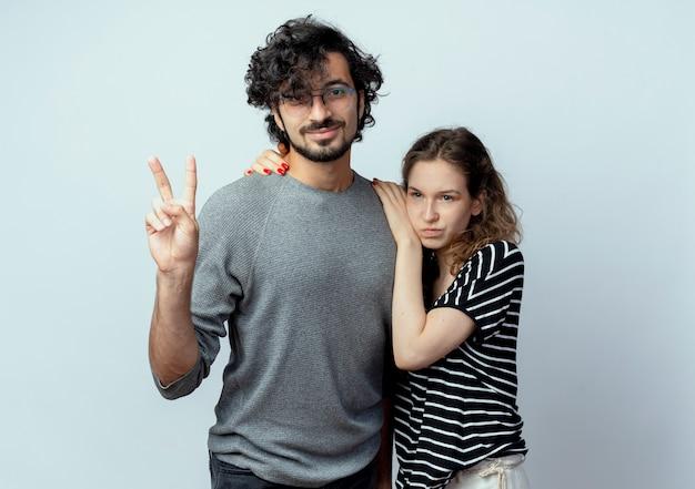 젊은 부부 남자와 여자는 서로 옆에 서있는 흰색 배경 위에 서 승리 기호를 보여주는 남자