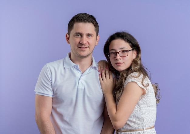 젊은 커플 남자와 여자가 함께 파란색 벽에 사랑에 행복 서