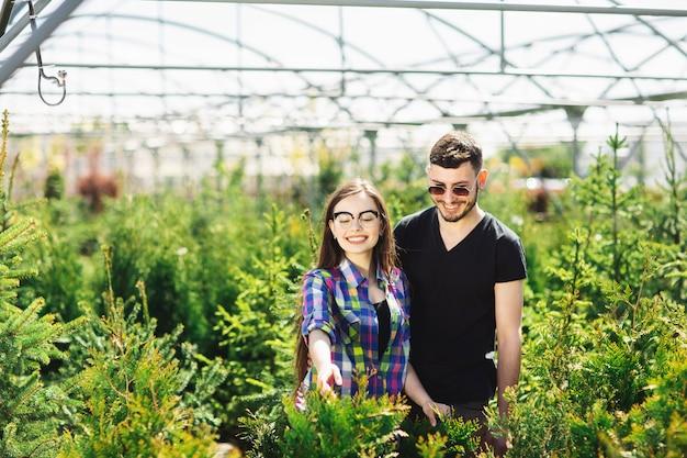 Молодая пара, мужчина и женщина, стоя вместе в садовом центре и выбирают растения