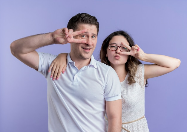 젊은 부부 남자와 여자가 함께 파란색 벽에 v 기호를 보여주는 행복하고 긍정적 인 카메라를보고 서