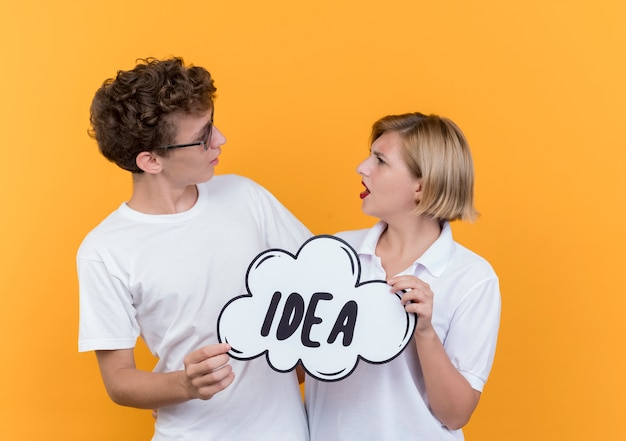 젊은 부부 남자와 여자는 오렌지 벽에 단어 아이디어와 연설 거품 기호를 들고 혼란 서로를보고 함께 서