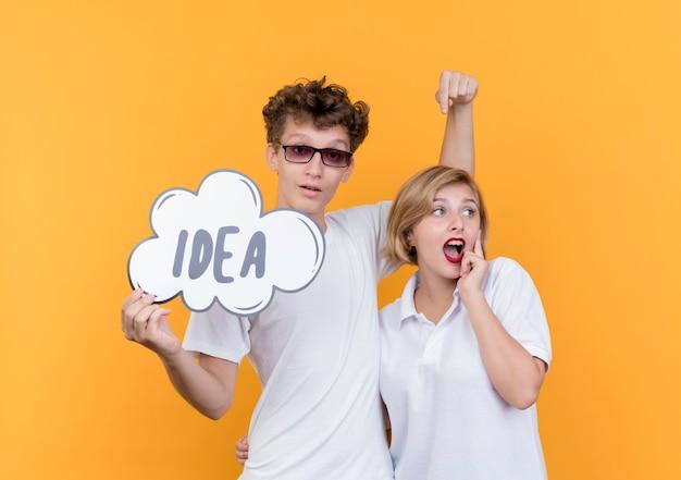 젊은 커플 남자와여자가 함께 서 행복 하 고 흥분 오렌지 벽에 단어 아이디어와 연설 거품 기호를 들고 웃 고