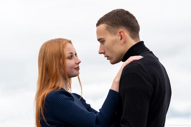 젊은 부부 남녀가 흐린 하늘을 배경으로 포옹을 하고 있다