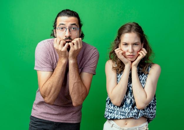 若いカップルの男性と女性は、緑の壁の上でショックを受けて不快になっているストレスと神経質な噛む爪