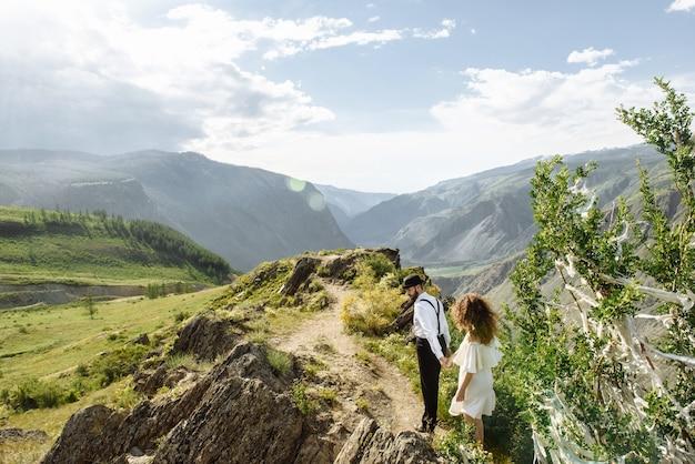 젊은 부부 남자와 여자 여행자는 산에서 손으로 걸어