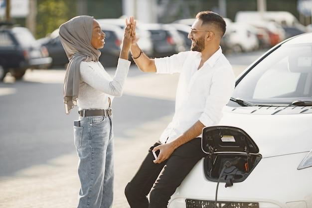 一緒に旅行する若いカップルの男性と女性。車の充電ステーションに立ち寄ってください。環境にやさしい車。