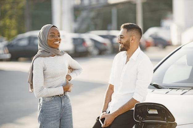 젊은 부부 남녀가 함께 여행합니다. 자동차 충전소에 들러보세요.
