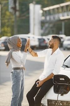 一緒に旅行する若いカップルの男性と女性。車の充電ステーションに立ち寄ってください。
