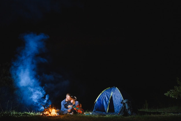 山の頂上にあるキャンプファイヤーを燃焼、熱烈な観光テントの近くに座っている若いカップルの男と女のトレベラー
