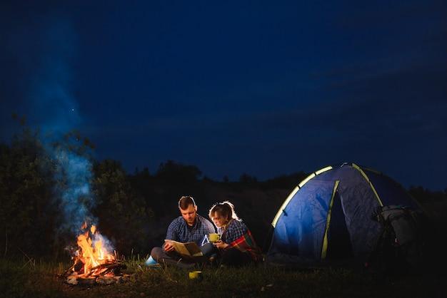 Молодая пара, мужчина и женщина, путешественники, сидящие возле светящейся туристической палатки, у горящего костра