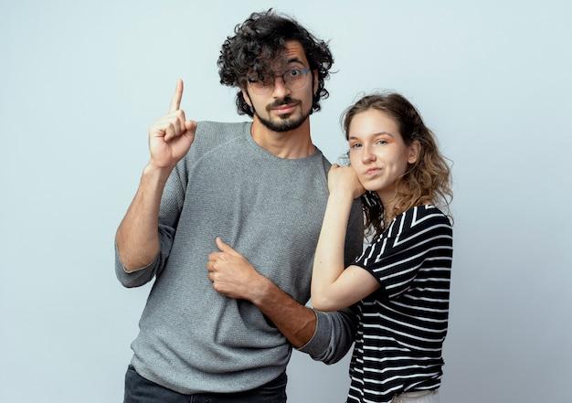彼のガールフレンドが白い背景の上に立って眉をひそめている間、若いカップルの男性と女性が人差し指を見せて隣同士でtsanding