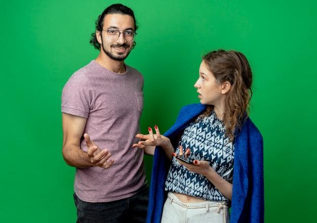 若いカップルの男性と女性、緑の背景の上に立っている彼女の笑顔のボーイフレンドを見て動揺した女性