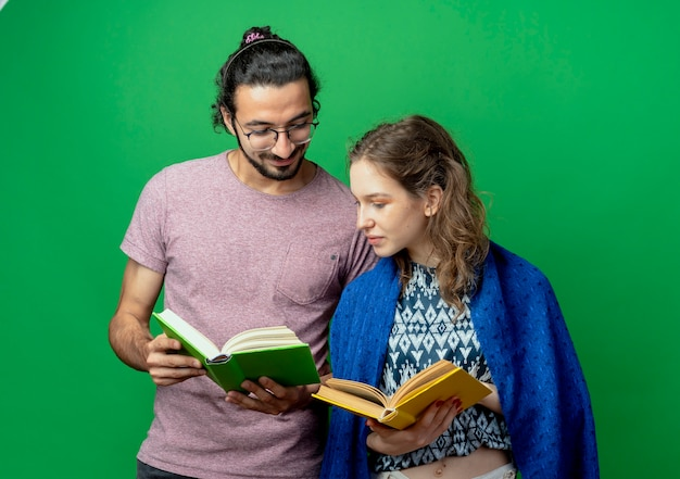 Молодая пара мужчина и женщина с одеялом, держа открытые книги, счастливые и позитивные, стоя на зеленом фоне