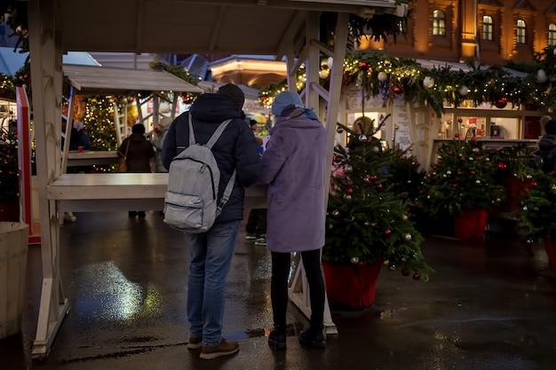 若いカップルの男性と若いカップルの男性と女性は、新年のマーケットプレイスストリートフェアのフードコートのテーブルに立って食べます。背面図。フェアやお正月飾りのバックグラウンドショップで
