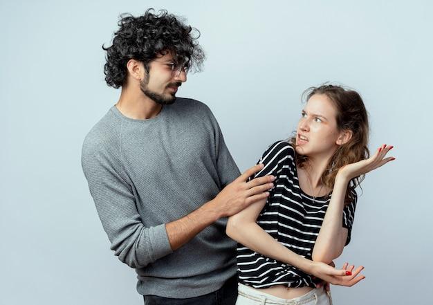 白い背景の上に腕を上げて立って戦った後、許しを求める若いカップルの男は不機嫌な女性