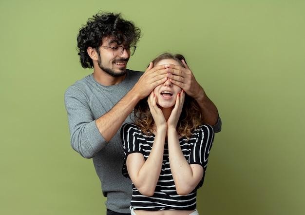 彼女が薄緑色の壁に幸せで興奮して笑っている間、若いカップルの男は女の子の目を閉じます