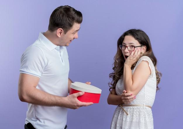 青い壁の上に立っている彼の驚いた最愛のガールフレンドにギフトボックスを与える若いカップルの男