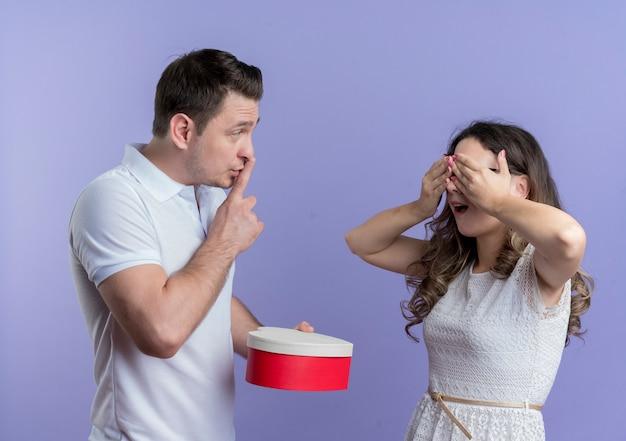 Giovane coppia uomo che dà un regalo alla sua amata fidanzata sorpresa in piedi sopra la parete blu