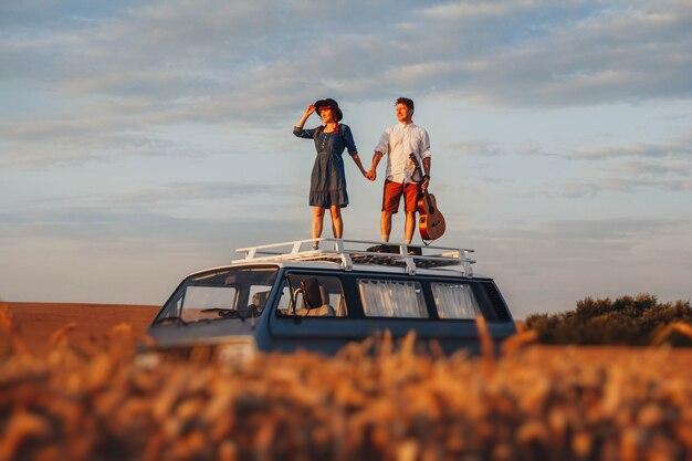 기타를 든 젊은 부부와 모자를 쓴 여성이 밀밭의 차 지붕에 서 있다