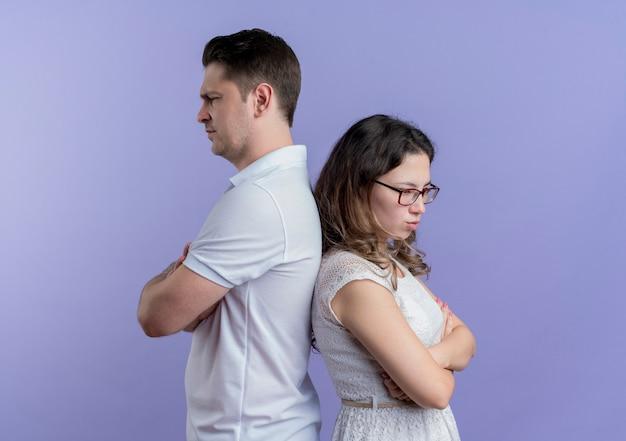 Coppia giovane uomo e donna schiena contro schiena aggrottando le sopracciglia sul blu
