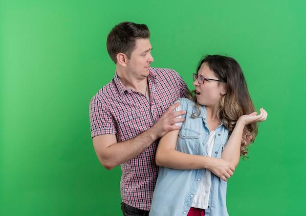 Giovane coppia uomo e donna in abiti casual uomo confuso chiedendo alla sua ragazza arrabbiata perdono in piedi sopra la parete verde