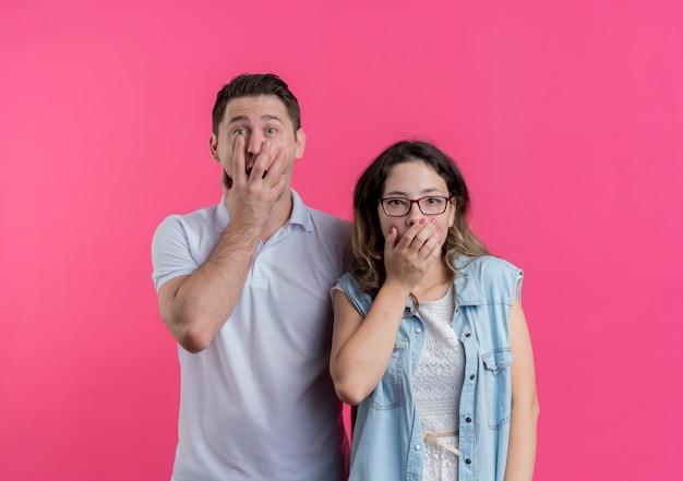 Giovane coppia uomo e donna in abiti casual che copre la bocca con le mani scioccate in piedi sopra il muro rosa