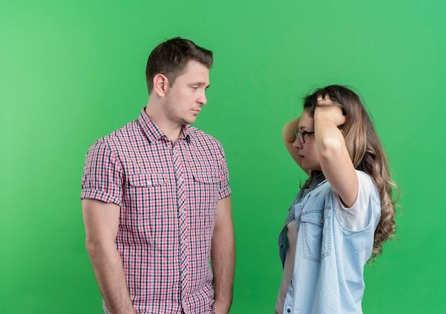 Giovane coppia uomo e donna in abiti casual uomo dispiaciuto con espressione triste guardando la sua ragazza confusa in piedi sopra la parete verde
