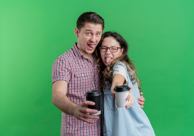 Young couple man and woman in casual clothes having fun together showing coffee cups standing over green wall