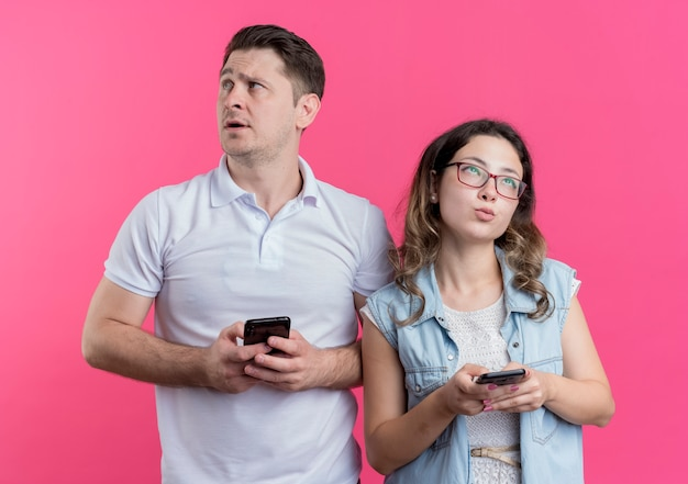Young couple man and woman in casual clothes holding smartphones looking asides with pensive expression standing over pink wall