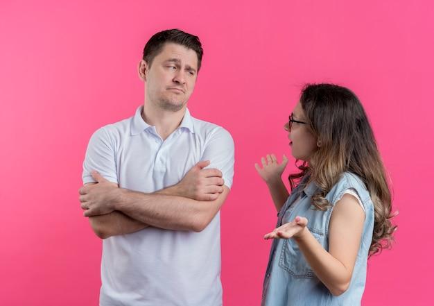 Giovane coppia uomo e donna in abiti casual uomo con le mani incrociate sul petto mentre la sua ragazza litiga con lui in piedi sul muro rosa