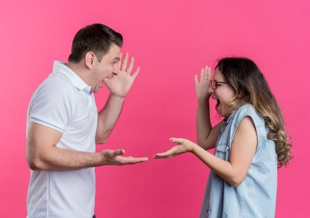 Giovane coppia uomo e donna in abiti casual che litigano gridando a vicenda sul rosa