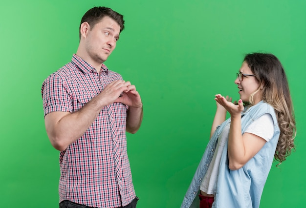 Young couple man and woman in casual clothes sad man showing heart gesture to her displeased girlfriend standing over green wall