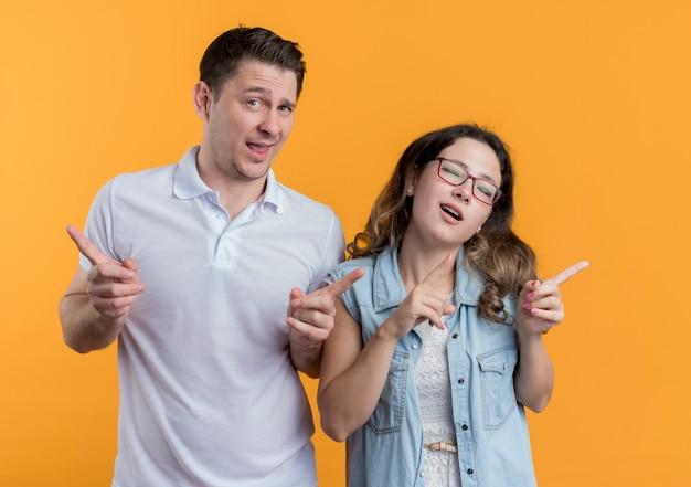 Giovane coppia uomo e donna in abiti casual sorridendo allegramente mostrando le dita indice gioiose e allegre sopra l'arancio