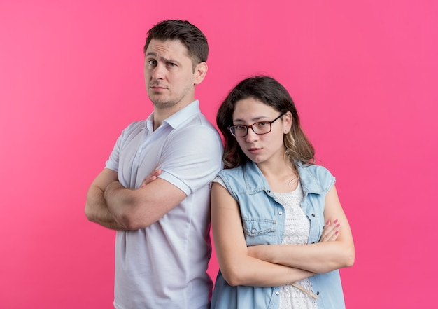 Coppia giovane uomo e donna in abiti casual in piedi schiena contro schiena scontento e accigliato sopra il muro rosa