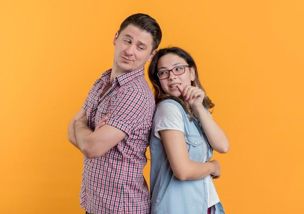 Coppia giovane uomo e donna in abiti casual in piedi schiena contro schiena sorridente sopra la parete arancione