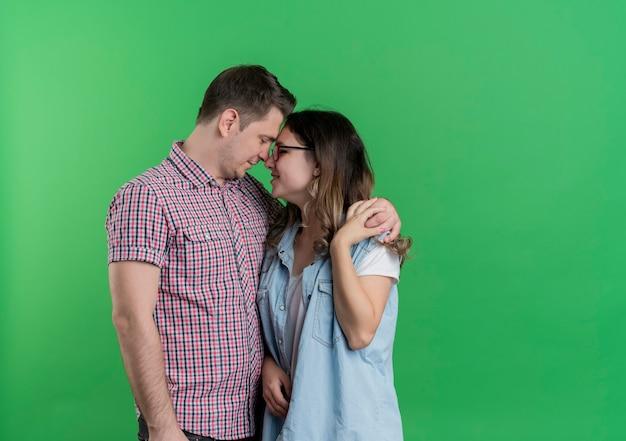 Coppia giovane uomo e donna in abiti casual che stanno insieme abbracciando felice nell'amore sopra la parete verde
