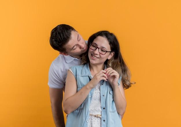 Giovane coppia uomo e donna in abiti casual in piedi insieme uomo che va a baciare la sua amata ragazza sorridente sopra la parete arancione