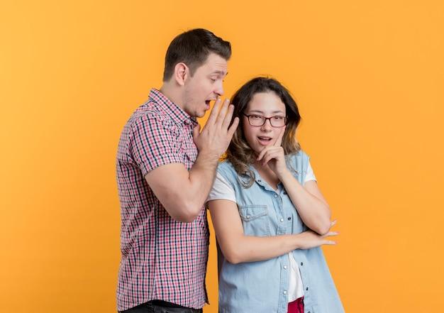 La giovane coppia uomo e donna in abiti casual ha sorpreso l'uomo che bisbiglia un segreto alla sua ragazza sull'arancia