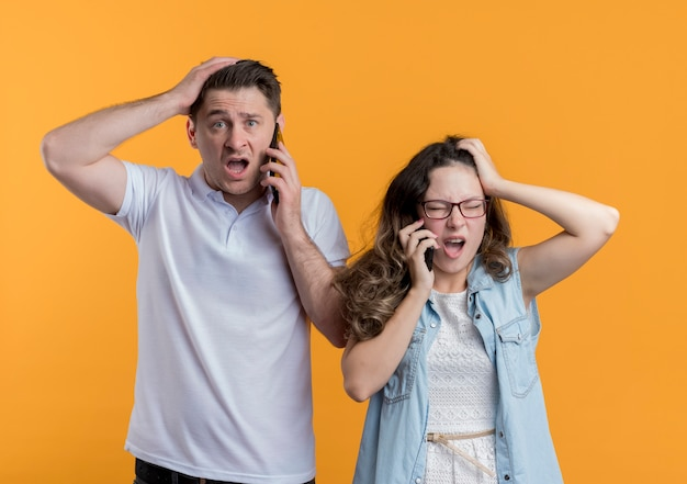 Young couple man and woman in casual clothes talking on mobile phones looking confused and very anxious touching their heads standing over orange wall