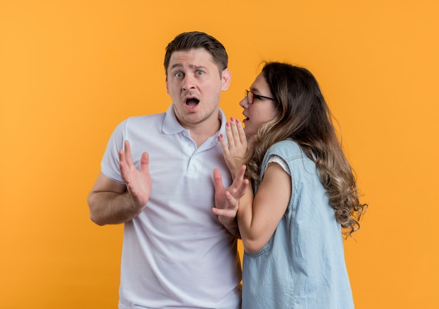 Young couple man and woman in casual clothes woman whispering a secret to her surprised boyfriend standing over orange wall