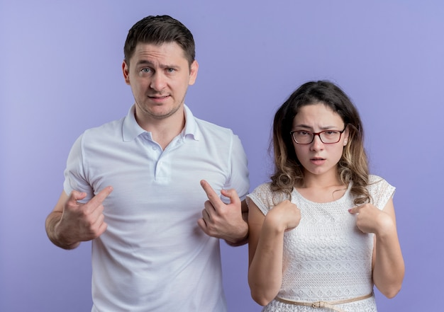 Young couple man and woman confused pointign with fingers at themselves over blue