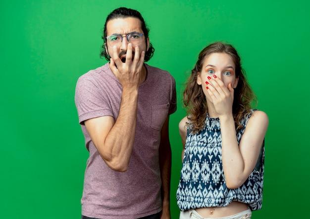 Giovane coppia uomo e donna, che copre le bocche con le mani scioccate in piedi sopra il muro verde