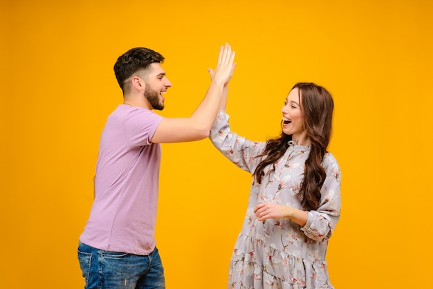 Young couple man and woman giving high five isolated